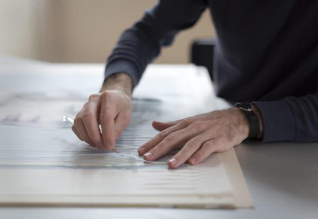 Hände, die Papierstreifen ineinander schieben