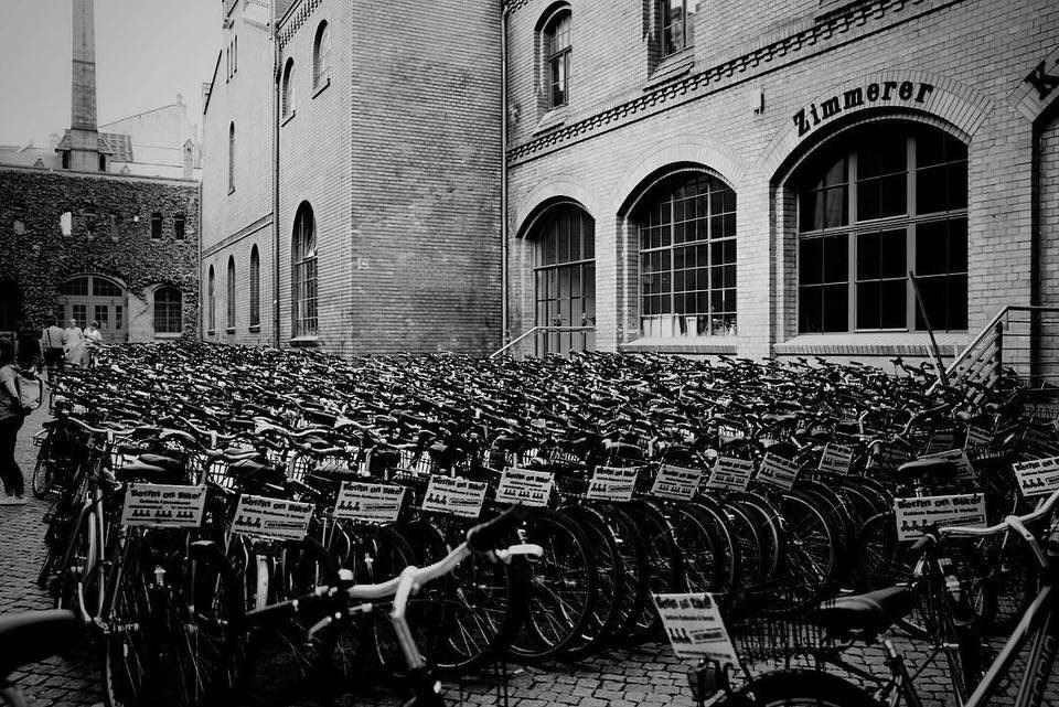 Schwarzweiße Aufnahme von ganz vielen Fahrrädern vor einer Industriekulisse.