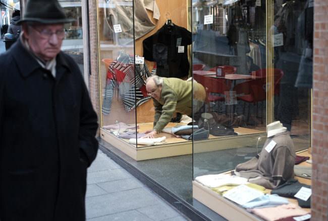 Ein Mann kniet im Schaufenster