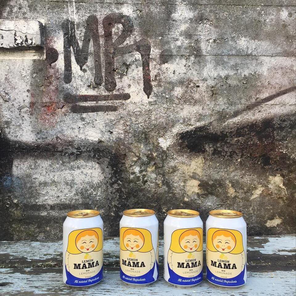 Vier Getränkedosen mit Matroskaaufdruck vor einer rustikalen Betonwand mit Graffito.