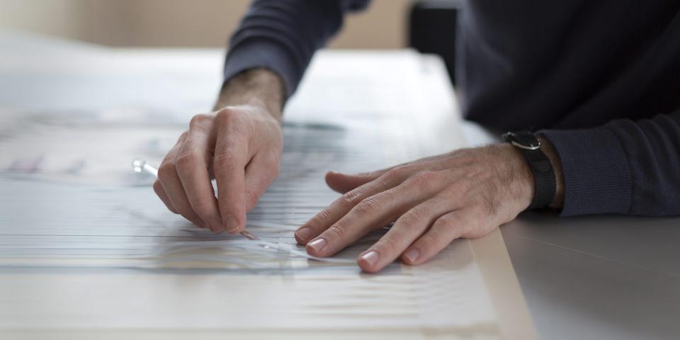 Nahaufnahme zweier Hände die Papier ineinander weben.