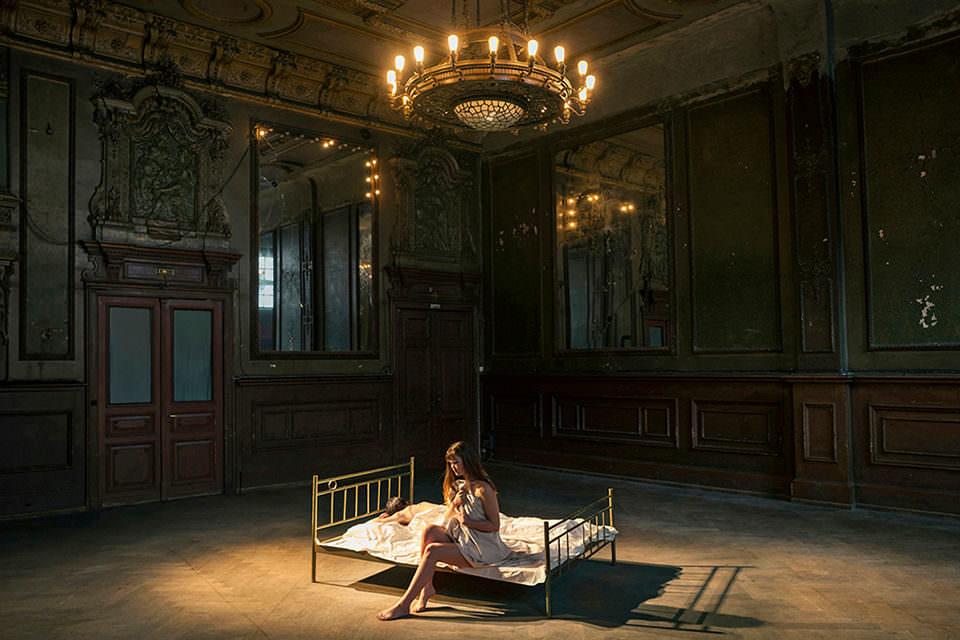 Eine Frau in einem großen Saal auf einem Bett