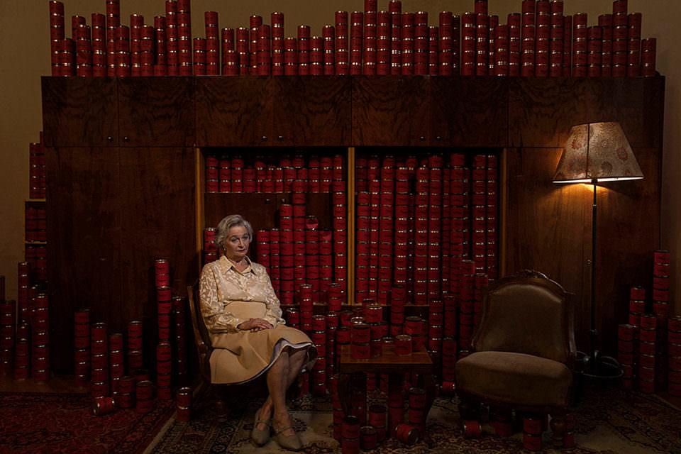 Eine Frau vor einer Schrankwand gefüllt mit Dosen