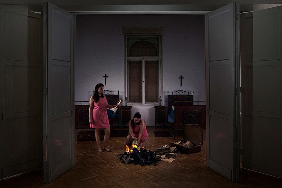 Zwei Frauen verbrennen etwas in einem Zimmer