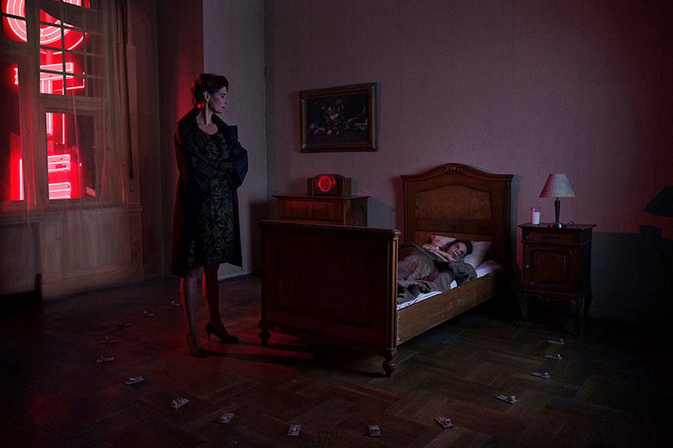 Eine Frau steht an einem Bett. Rundherum Mäusefallen