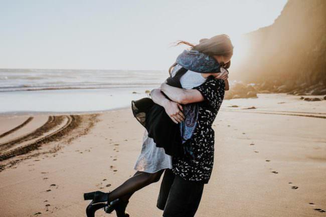 Ein paar dass sich schwungvoll umarmt bei Sonnenuntergang an einem Strand.