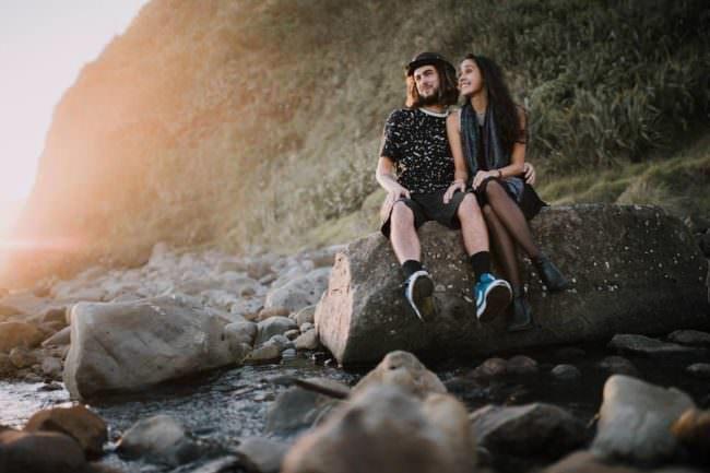 Ein Paar, das bei Sonnenuntergang auf einem Stein sitzt und lacht.