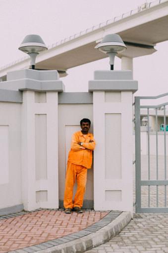 Ein Mann in orange lehnt an einer Mauer