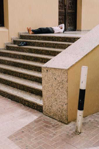 Ein Mann schläft auf einer Treppe
