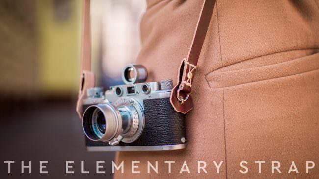 Eine Filmkamera an einem Kameragurt aus Leder