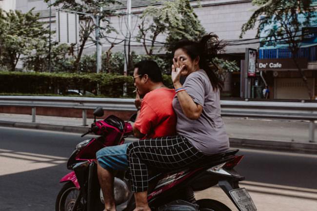 Zwei Menschen auf einem Motorrad winken
