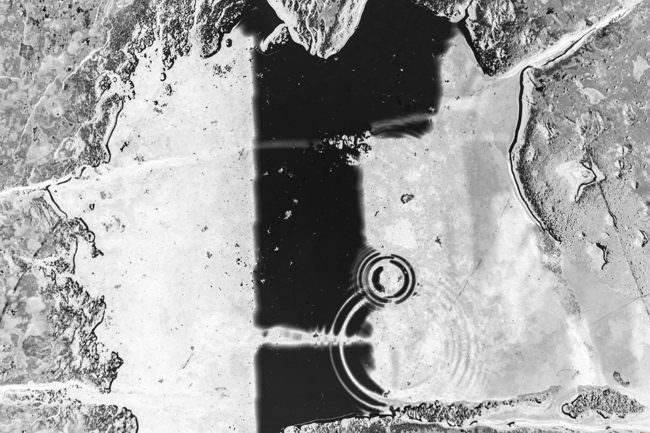 Schwarzweißaufnahme einer Reflexion in einer Pfütze, in die zwei Tropfen gefallen sind, die Kreise werfen.