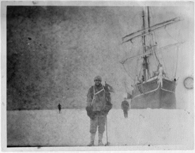 Ein Mann im Eis vor einem Schiff