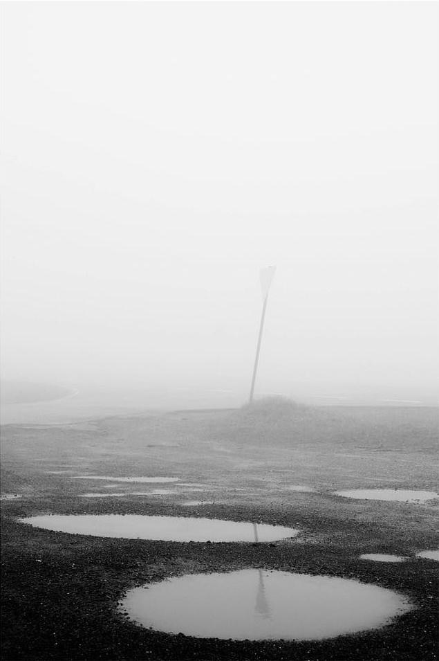 Karge Landschaft mit großen Pfüten im Nebel.