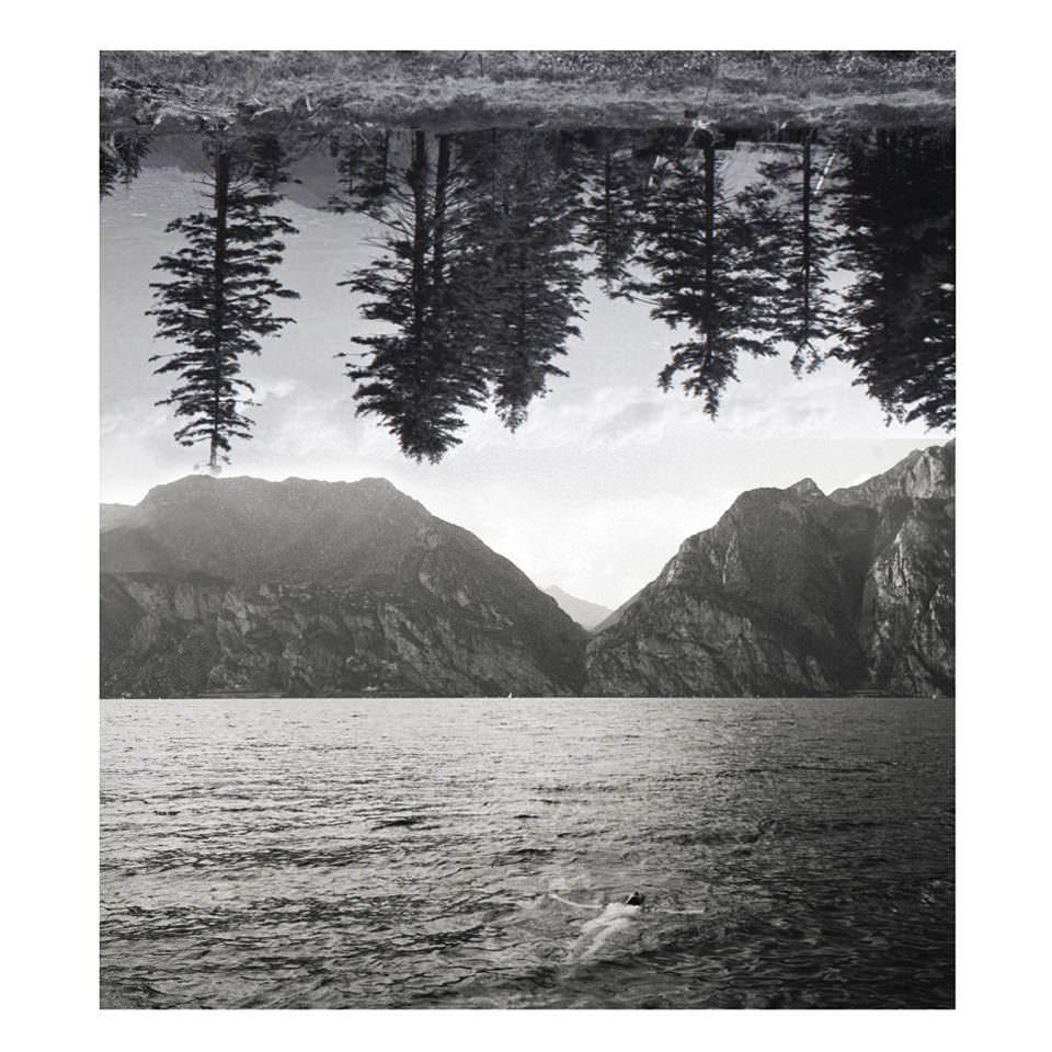 Doppelbild: Am Himmel ein auf dem Kopf stehender Tannenwald, darunter eine Person, die nackt im Wasser vor einer Bergkulisse treibt.