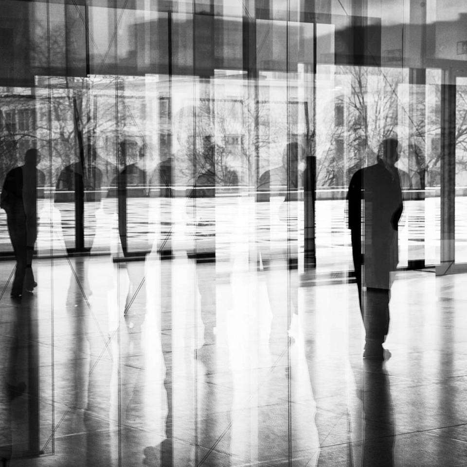 Mehrfachbelichtung: Person, Fensterfront, Spiegelungen.