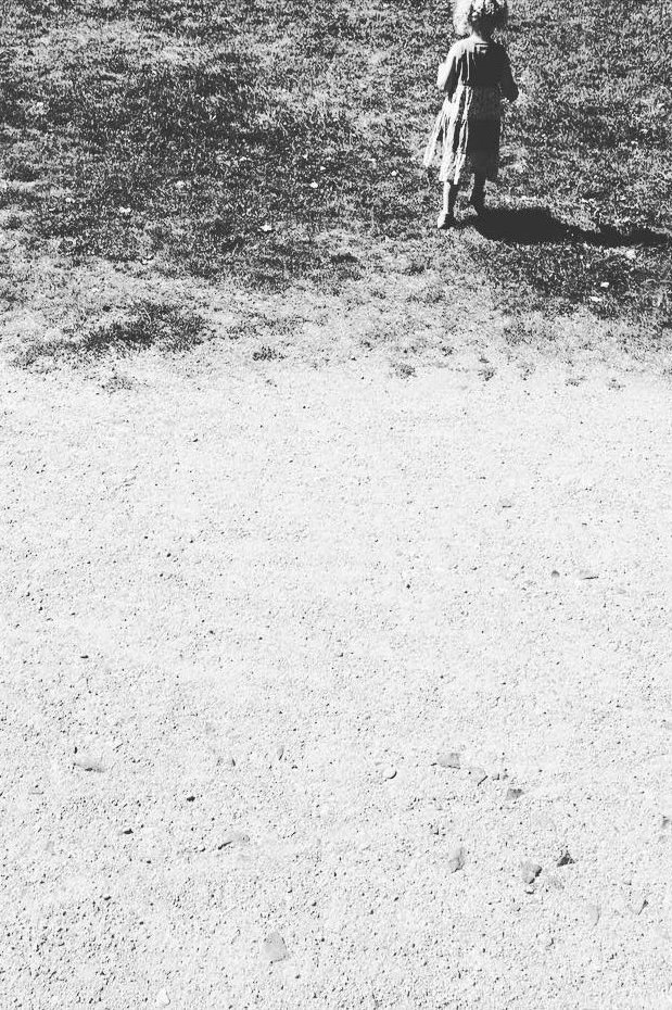 Kind auf Resten einer Wiese, die zum Strand wird.