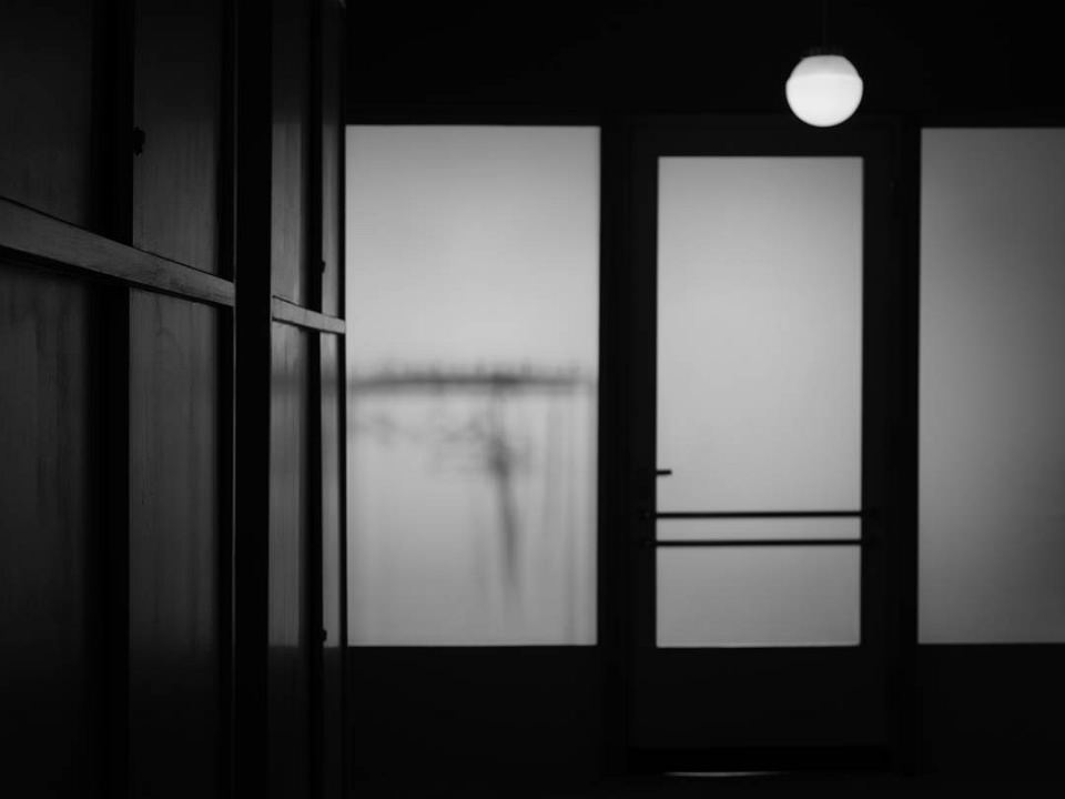 Licht scheint durch eine Glastür und Fenster in einen dunklen Raum.