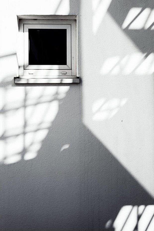 Licht- und Schattenspiel auf einer weißen Fassade mit kleinem Fenster.