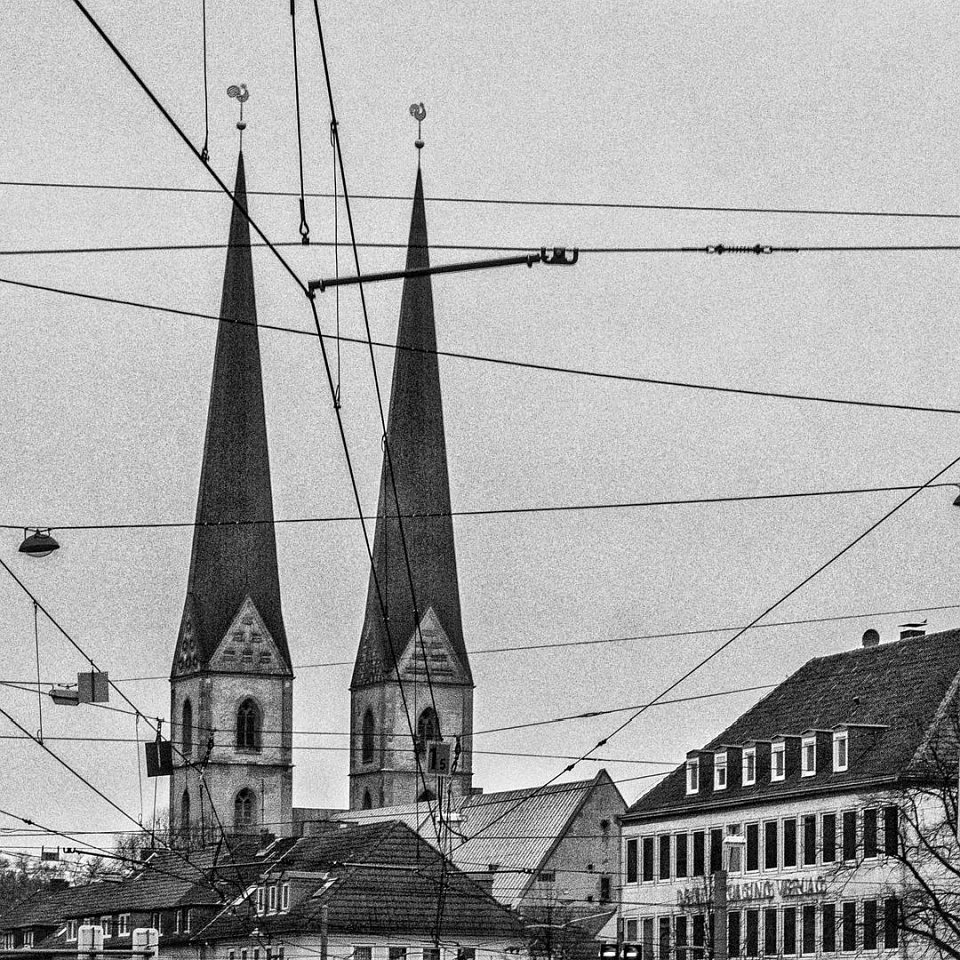 Oberleitungen vor den Dächern einer Stadt mit Kirche.