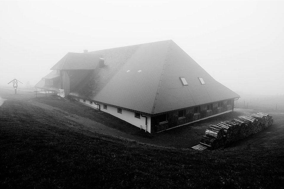 Gebäude mit hohem Satteldach im Nebel.
