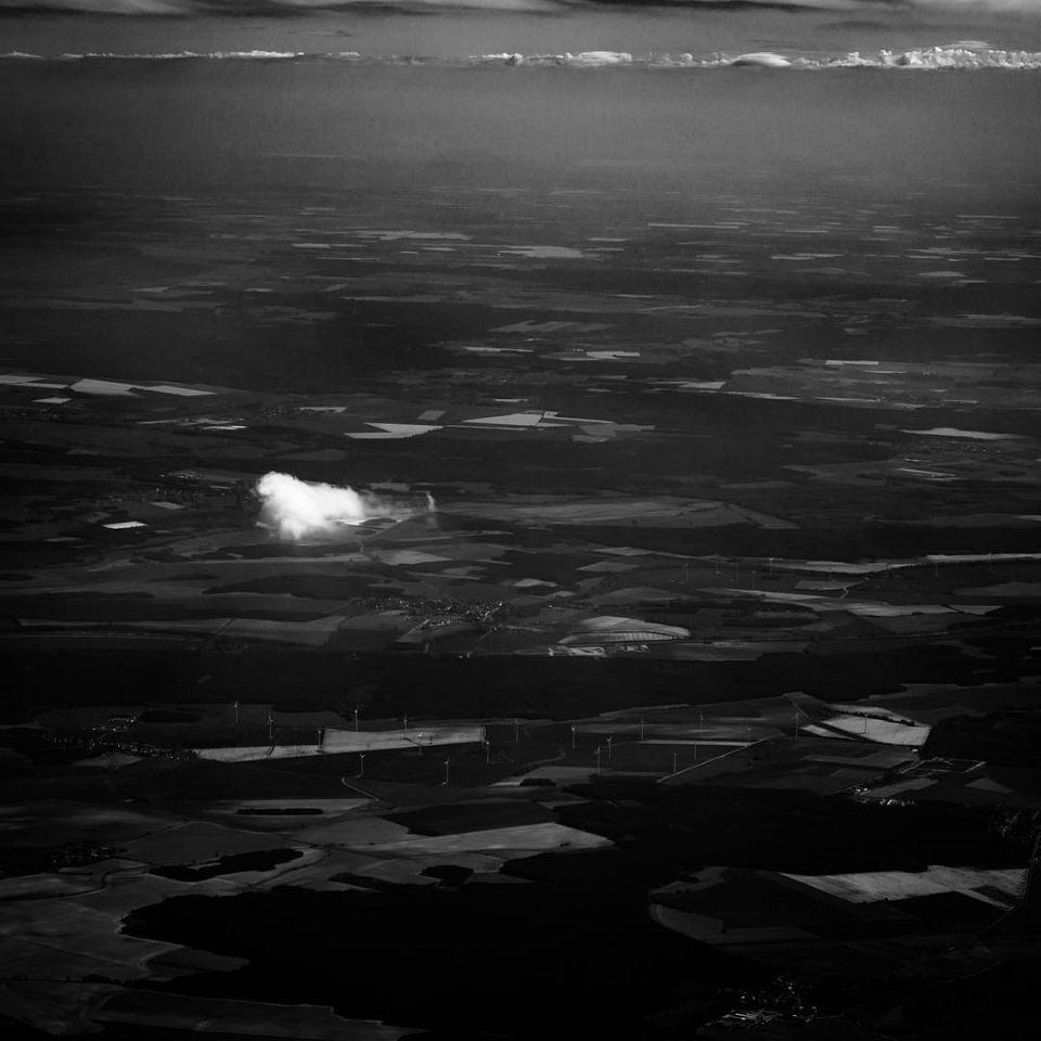 Luftaufnahme einer ländlichen Region aus großer Höhe, darüber eine einzelne kleine Wolke.