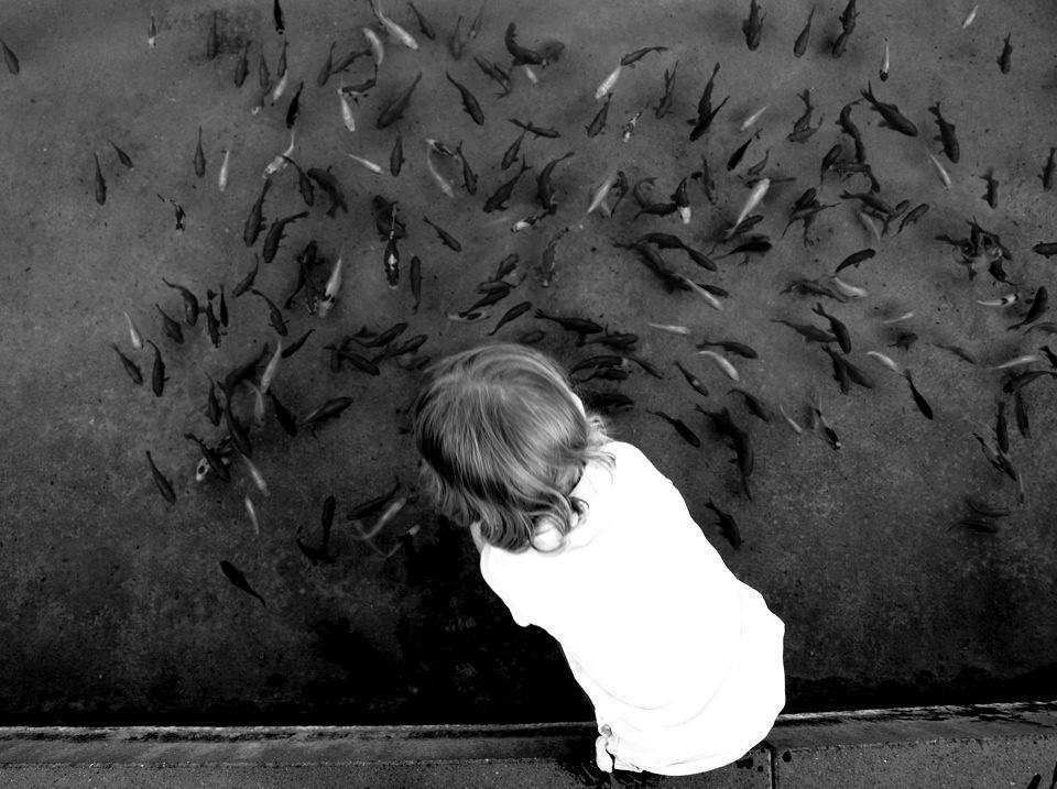Kind an einem Fischteich.