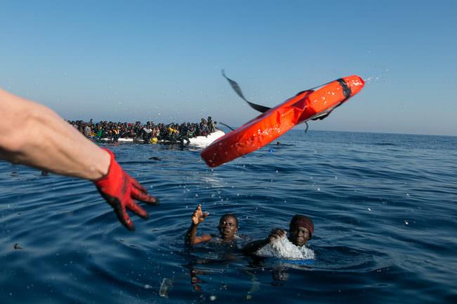 Eine Rettungsweste wird von einem Boot aus zu Menschen im Wasser geworfen