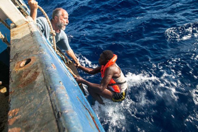 Ein Mann rettet einen anderen aus dem Wasser