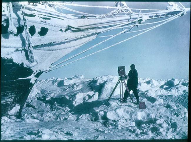 Eine Person fotografiert ein Schiff im Eis