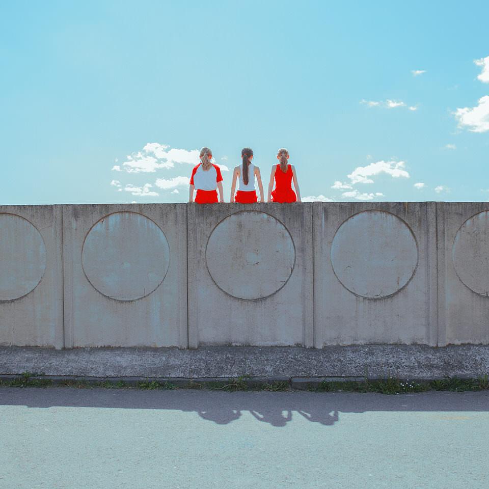 Drei Kinder sitzen auf einer Mauer