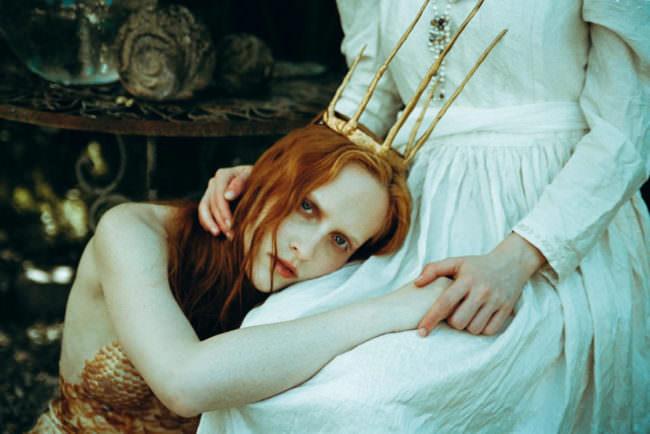 Eine Frau mit Krone liegt auf einem Schoß