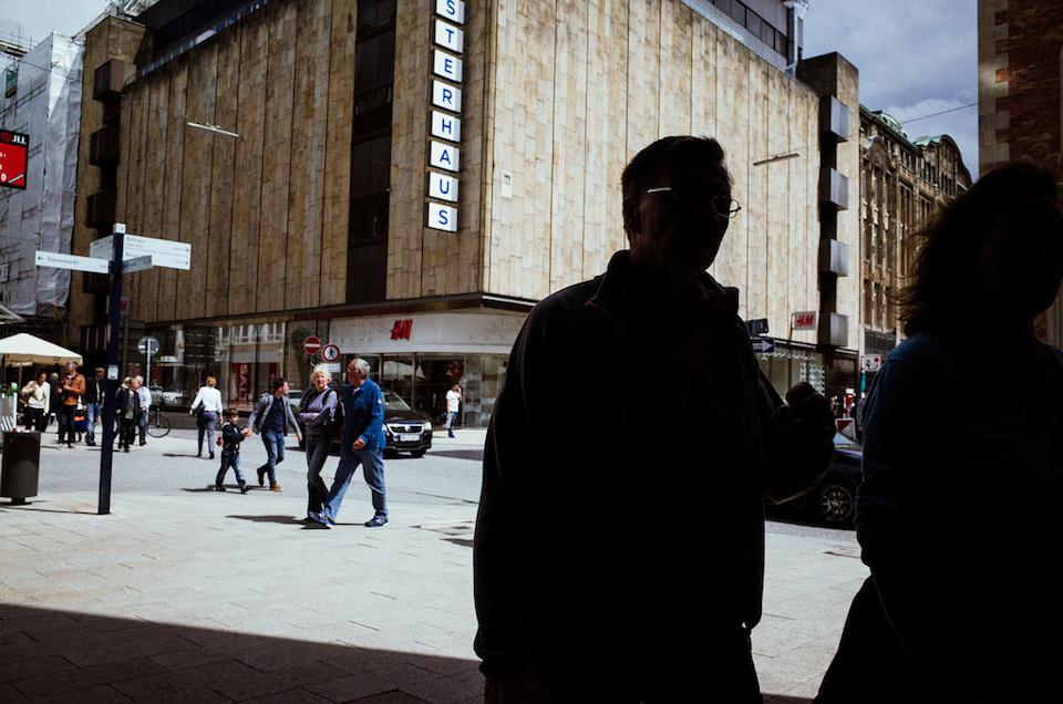 Menschen die auf einem großen Platz vor einem Kaufhaus stehen.