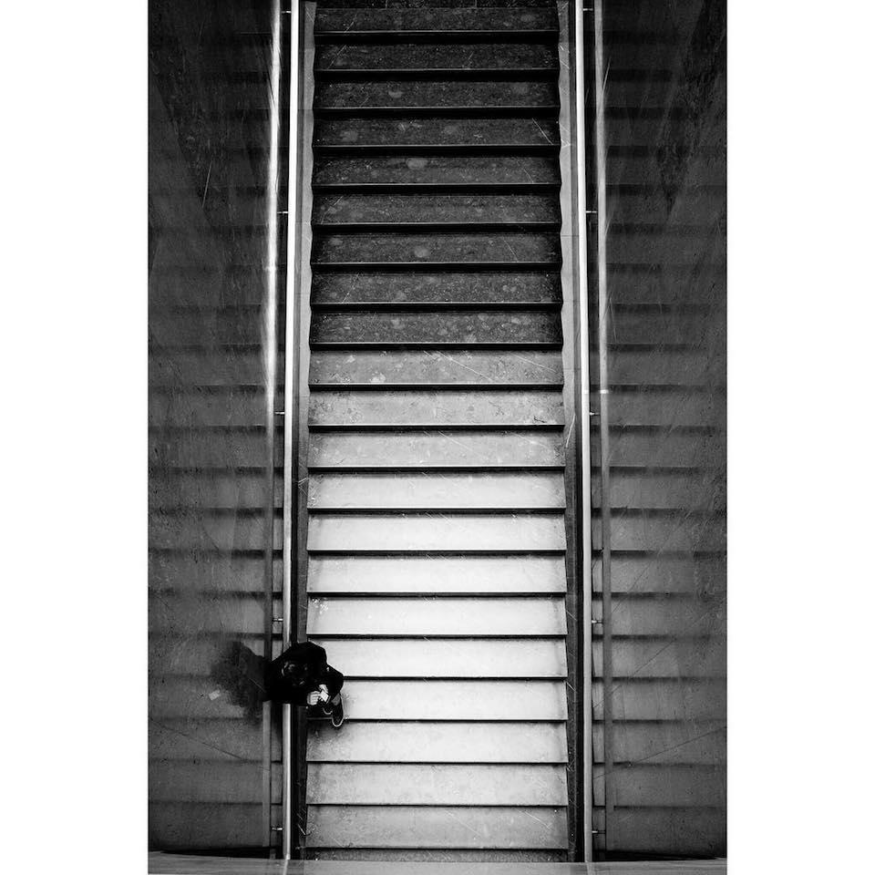 Eine Treppe aus der Vogelperspektive, auf der ein Mensch steht.