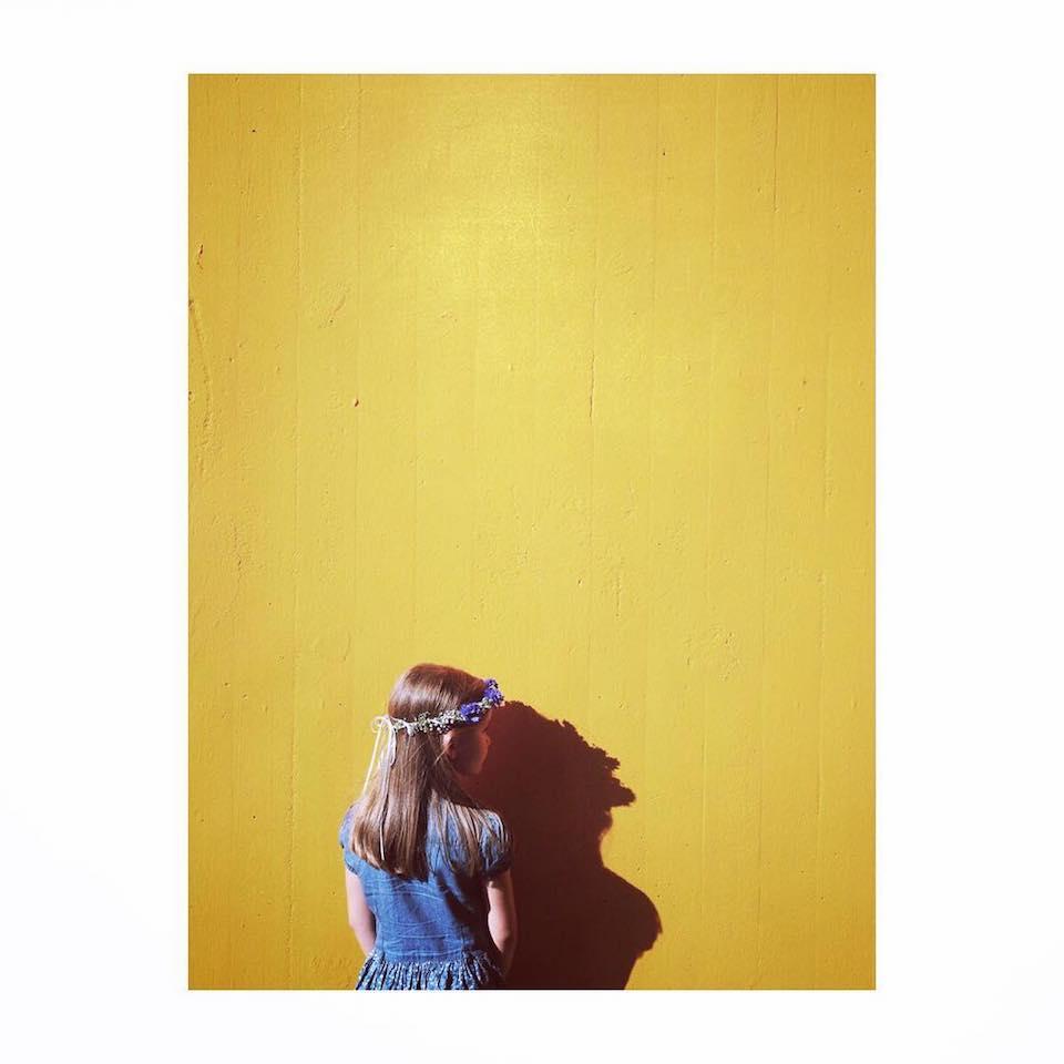 Ein Kind mit einem Blumenkranz auf dem Kopf, das vor einer gelben Wand steht.