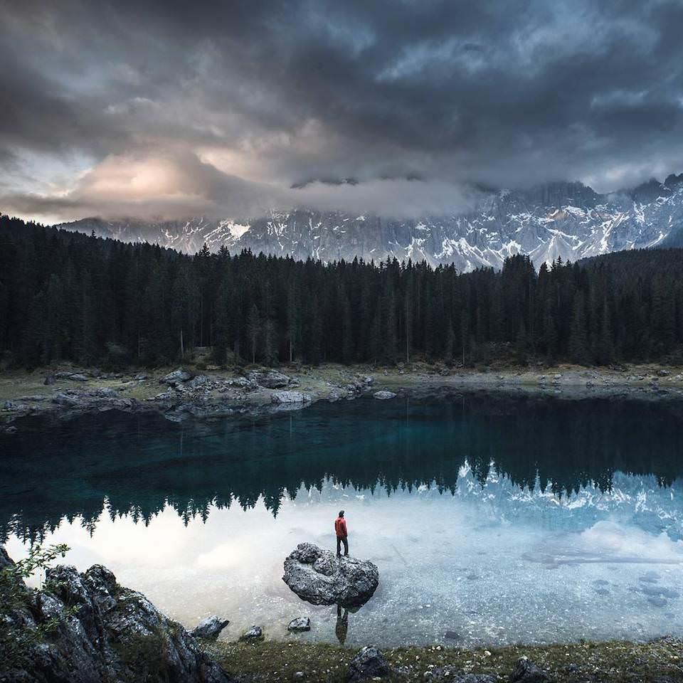 Ein Mensch steht auf einem Felsen in einem See in den Bergen.