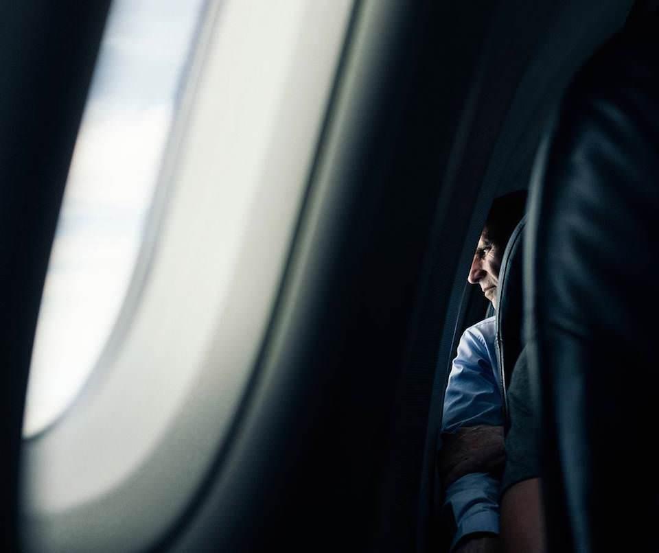 Ein Mann blickt aus dem Fenster eines Flugzeuges.