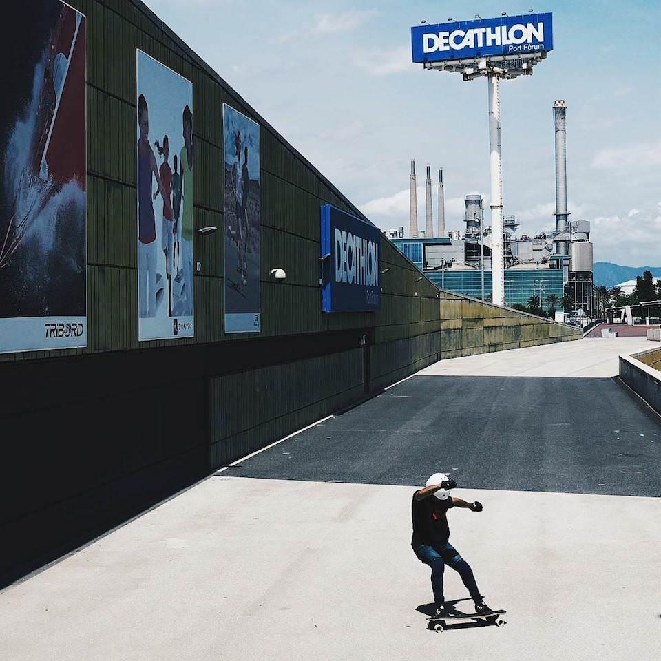 Ein Mensch auf einem Skateboard vor einer Industrieszene.