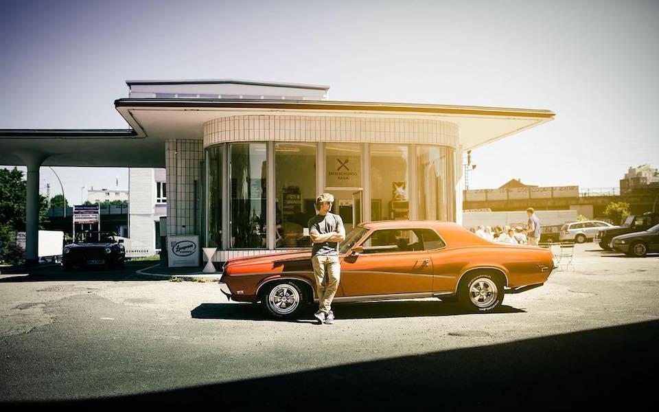 Ein Mann lehnt an einem Auto vor einem Gebäude.