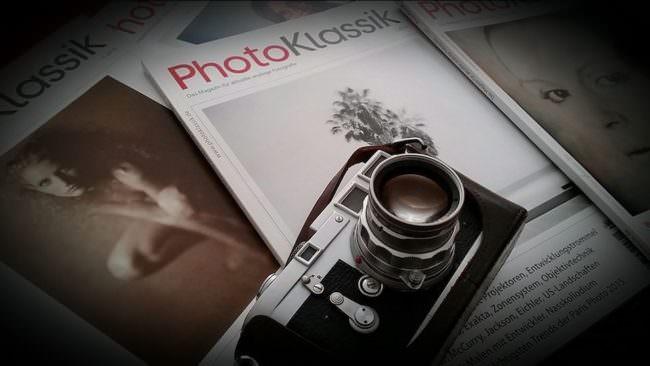 mehrere Magazine, auf denen eine Filmkamera liegt.