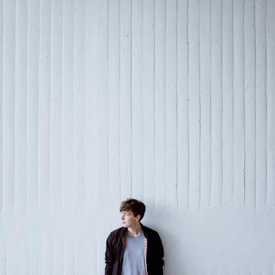 Portrait eines Mannes, der an einer Wand lehnt und nach links blickt.