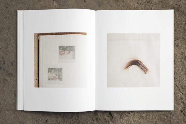 Aufgeschlagenes Buch mit zwei abgebildeten Fotografien. Eine zeigt einen Teil eines Fotoalbums das Andere eine Haarsträhne.