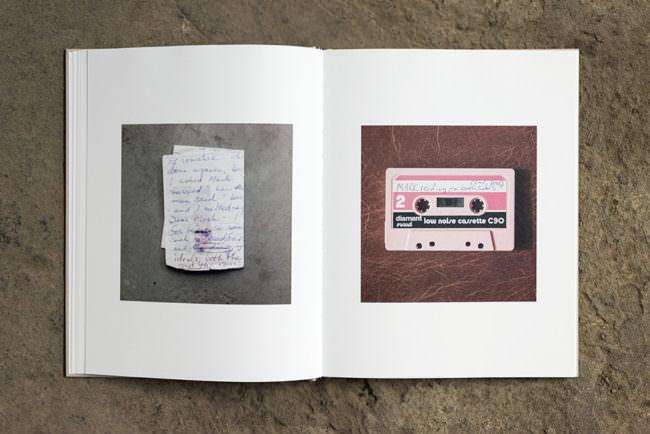 Aufgeschlagenes Buch das zwei Fotografien zeigt. Eine von einem Zettel und eine von einer Kassette.