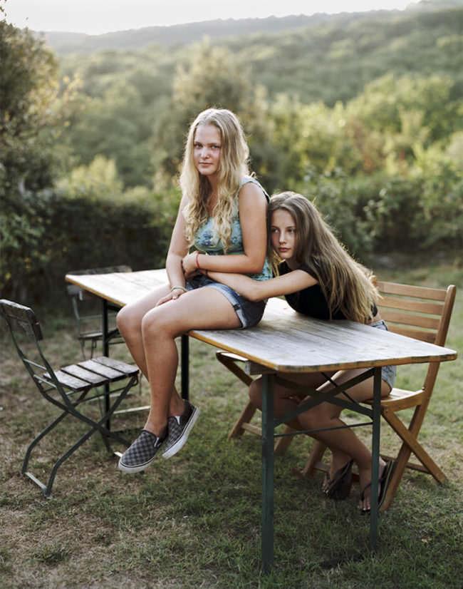 Portrait zweier junger Mädchen, im Freien sitzend. Eine auf dem Tisch und eine auf einem Stuhl, sich gegenseitig haltend.
