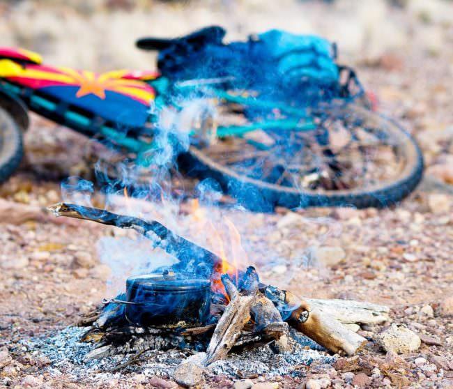 Ein Lagerfeuer mit einem Fahrrad im Hintergrund
