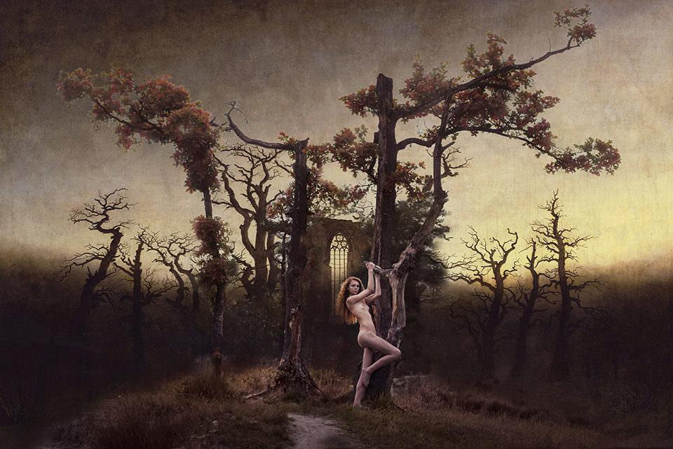 Eine nackte Frau vor einer düsteren Landschaft an einen Baum gelehnt