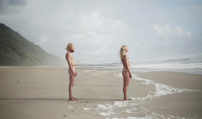 Zwei Menschen am Strand verbunden durch Stricke