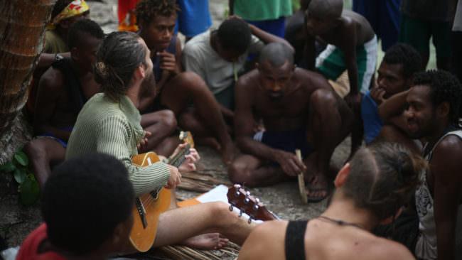 Ein Mann mit Gitarre in einer Gruppe Menschen
