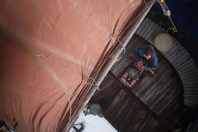 Ein Mann sitzt auf einem Segelboot