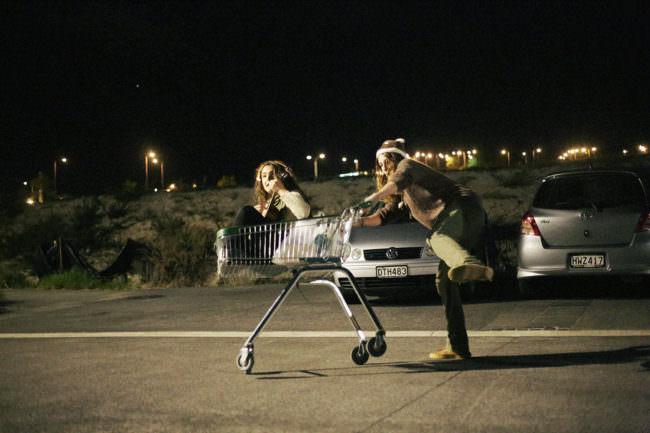 Eine Frau schiebt einen Einkaufswagen. Darin sitzt eine Frau mit Gitarre